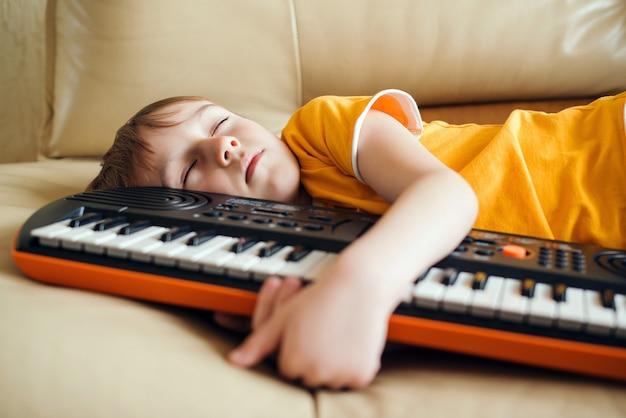 Słodkie dziecko zmęczone nauką gry na syntezatorze. hobby i wypoczynek dla dzieci. przyszły zawód.