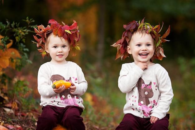 Słodkie dziewczynki bliźniaczki bawiące się szpikiem warzyw w jesiennym parku. jesienne zajęcia dla dzieci. halloween i święto dziękczynienia zabawa dla rodziny.