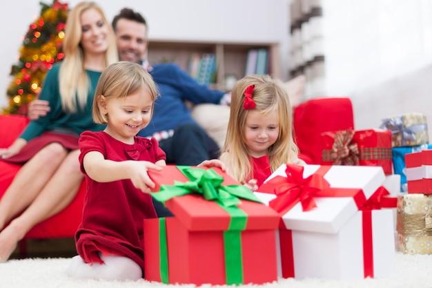 Słodkie dziewczynki otwierające świąteczne prezenty
