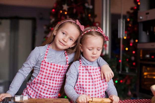 Słodkie dziewczynki przygotowujące pierniki na boże narodzenie
