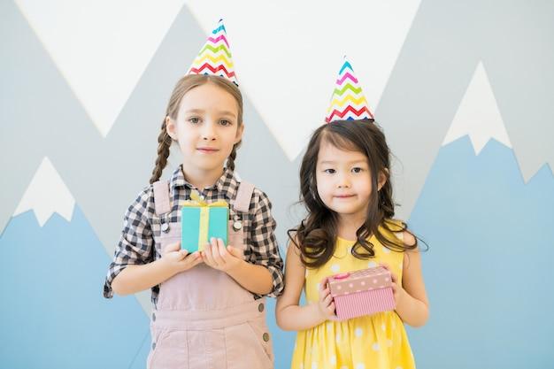 Słodkie dziewczynki w kolorowych czapeczek