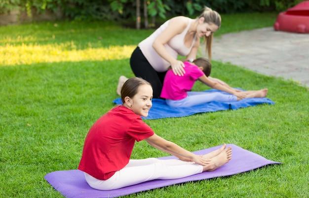 Słodkie dziewczyny ćwiczą jogę na trawie na podwórku