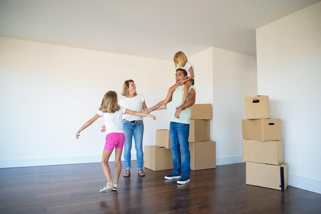 Słodkie dziewczyny i ich mama pokazują podekscytowanemu tacie nowe mieszkanie
