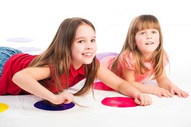 Słodkie dziewczyny leżą na grze twister