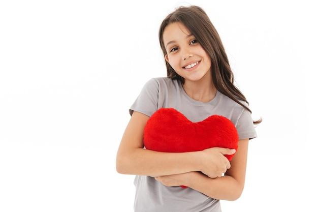 Słodkie dziewczyny stojącej na białym tle trzymając serce w ręce.