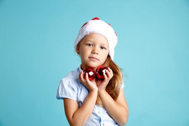 Słodkie dziewczyny w kapeluszu nowy rok z czerwonymi bombkami na białym tle.
