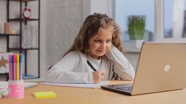 Słodkie dziewczyny w szkole podstawowej studiuje w domu przy użyciu komputera przenośnego. uczennica ma lekcję online.