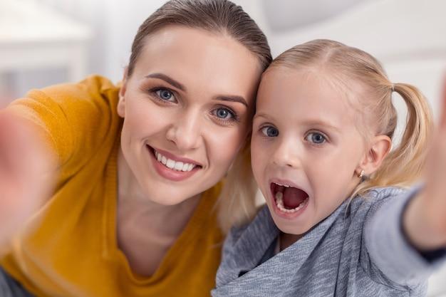 Słodkie emocje. wesoła, beztroska, miła matka i córka patrzą na mrówkę, gdy dziewczyna otwiera usta i bawi się
