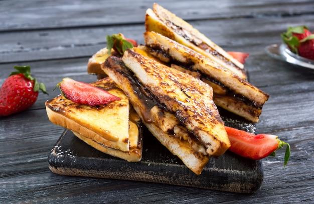 Słodkie francuskie tosty z bananem, czekoladą, truskawkami na drewnianej powierzchni. smaczne śniadanie. widok z góry