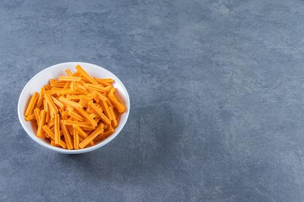 Słodkie frytki ziemniaczane w misce, na marmurowym tle.