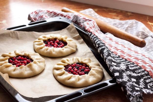 Słodkie galettes z czarnym bzem i borówkami na blasze gotowe do pieczenia