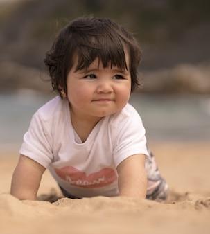Słodkie hiszpańskie dziecko na piaszczystej plaży