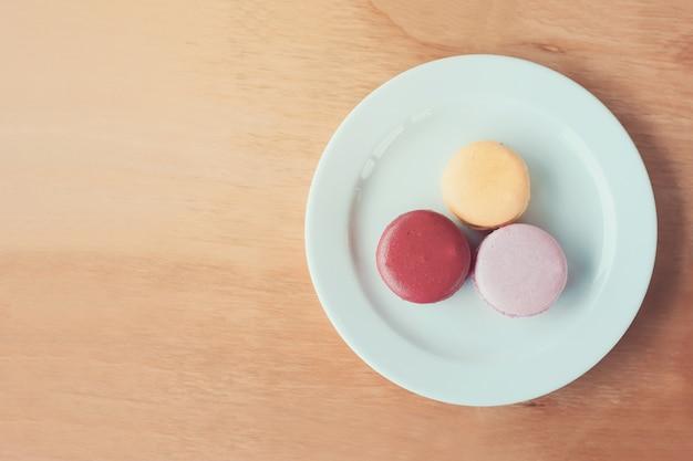 Słodkie i kolorowe francuskie makaroniki na tle drewna
