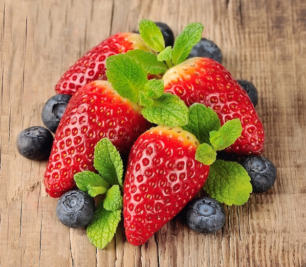 Słodkie jagody na drewnianej teksturze. truskawka i jagody z miętą.