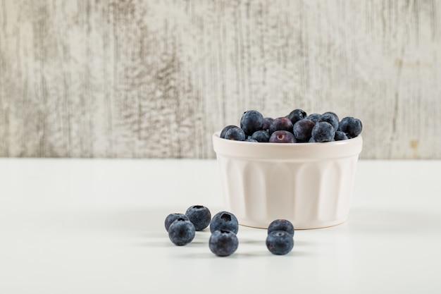 Słodkie jagody w widoku z boku białe miski na tle grunge i biały