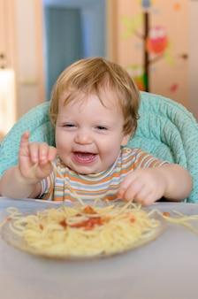 Słodkie jednoroczne dziecko zjada spaghetti na krześle dla dzieci.