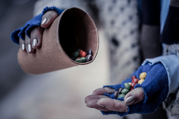 Słodkie jedzenie. zbliżenie dłoni biednej bezdomnej kobiety wypełnionej słodyczami