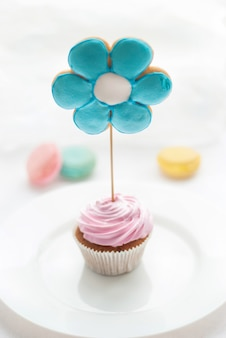 Słodkie kolorowe ciastko z ciasteczkami w kształcie kwiatka na białym talerzu i makaronikiem na tle. wysoki widok. desery na dobry nastrój do herbaty
