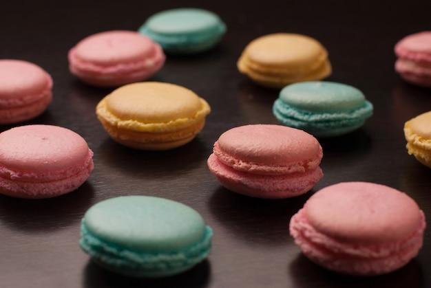Słodkie kolorowe makaroniki na tle czarnego stołu z odbicia. desery na dobry nastrój