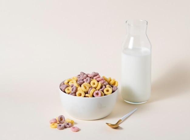 Słodkie kolorowe płatki kukurydziane pierścienie w białej misce z łyżką i butelką mleka na żółtym tle. widok z przodu i obraz miejsca kopiowania