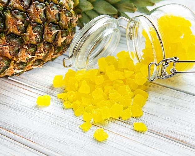 Słodkie kostki sukadu ananasa na białej drewnianej powierzchni
