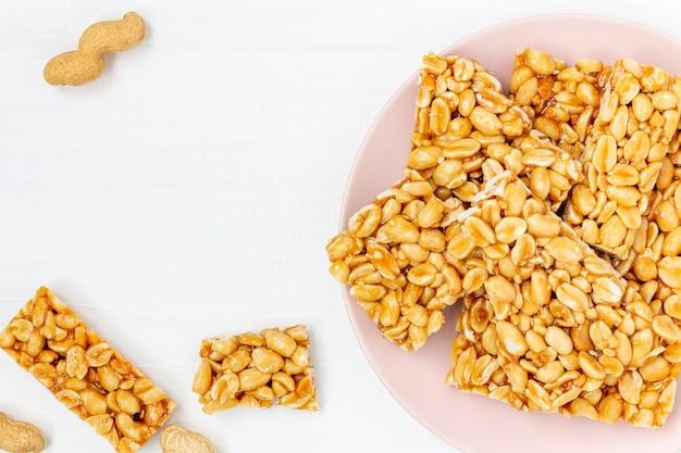 Słodkie kozinaki orzechowe (gozinaki) na naczyniu na białym stole