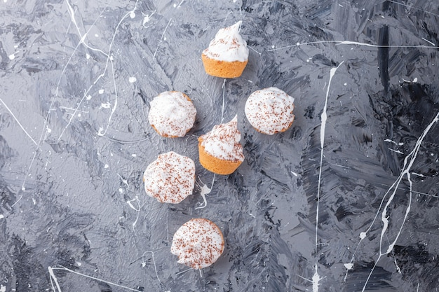 Słodkie kremowe mini babeczki rozrzucone na marmurowym tle.