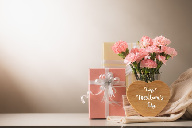 Słodkie kwiaty goździka i prezent na stole