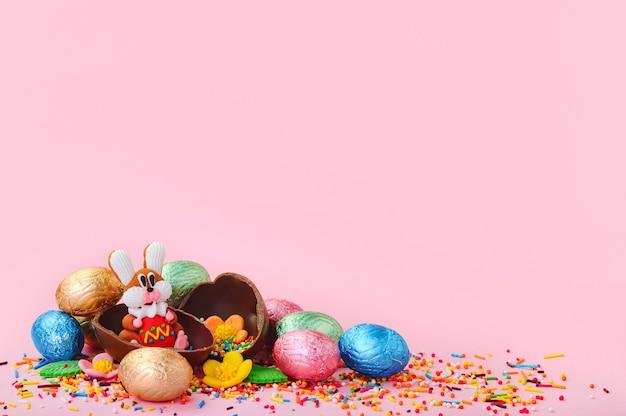 Słodkie kwiaty, słodki króliczek i czekoladowe jajka w folii na różowym tle z pustym miejscem na inspirację. kompozycja wielkanocna.