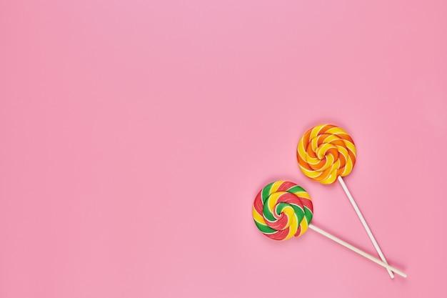 Słodkie lizaki na różowym tle, miejsce. uwielbiam kolorowe cukierki w koncepcji dzieciństwa