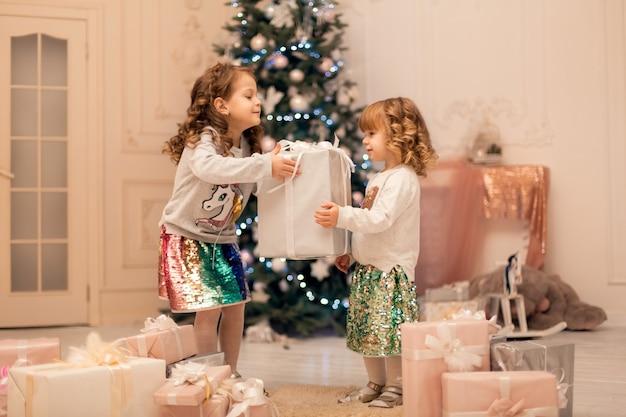 Słodkie małe bliźniaczki świętują razem święta bożego narodzenia.