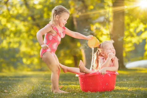 Słodkie małe blond dziewczyny bawiące się wodą rozpryskową na boisku w lecie