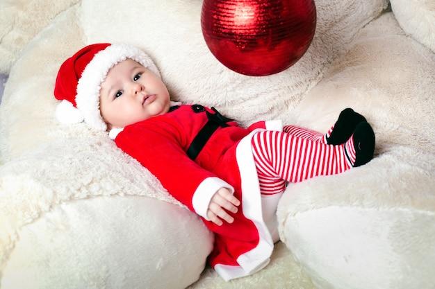 Słodkie małe boże narodzenie dziecko w ramionach pluszowego misia w kostiumie świętego mikołaja i bawiące się zabawką noworoczną