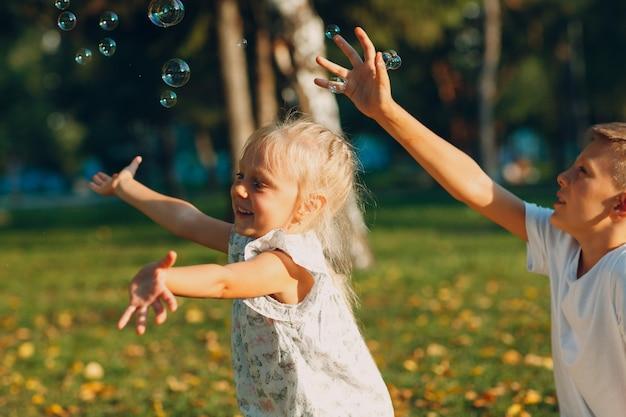 Słodkie małe dzieci chłopiec i dziewczynka dmuchanie baniek w parku jesień w słoneczny dzień.
