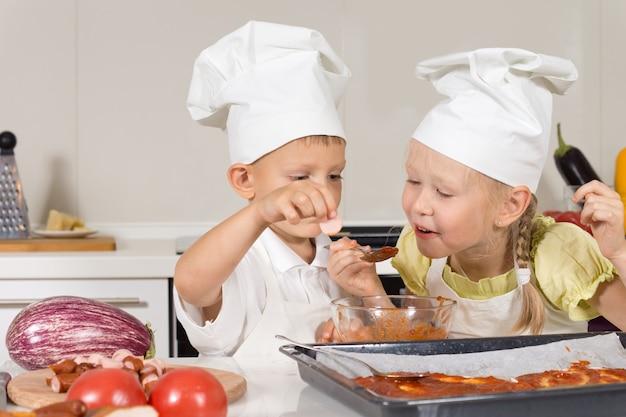 Słodkie małe dzieci do degustacji sosu do pizzy w kuchni