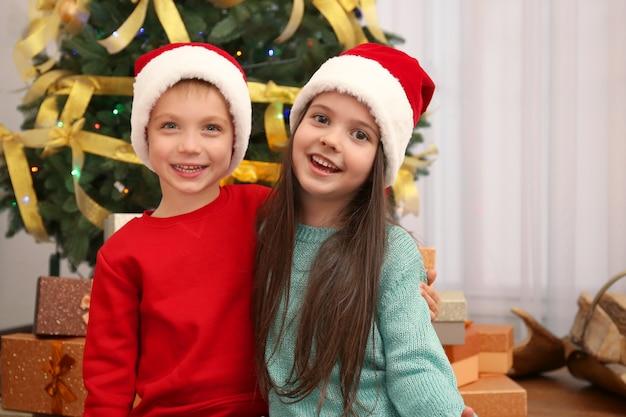 Słodkie małe dzieci w czapkach mikołaja w domu
