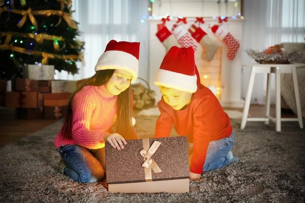 Słodkie małe dzieci w czapkach mikołaja z prezentem świątecznym w domu