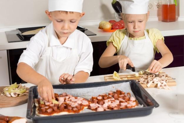 Słodkie Małe Dzieci W Stroju Szefa Kuchni, Co Smaczna Pizza W Kuchni. Premium Zdjęcia