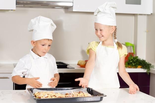 Słodkie małe dzieci zrobiły pyszną pizzę na białym stole