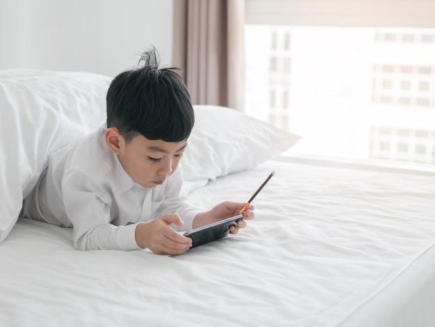 Słodkie małe dziecko azjatyckie koncentruje się na smartphone leżąc na łóżku