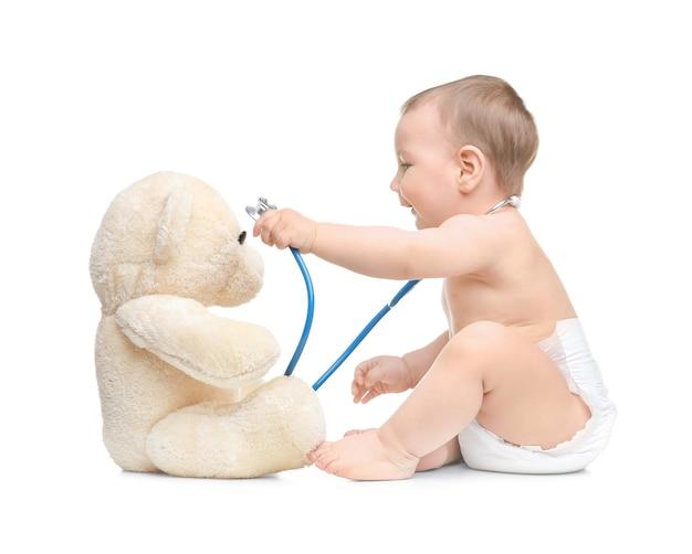 Słodkie małe dziecko bawi się stetoskopem i misiem zabawka. koncepcja opieki zdrowotnej