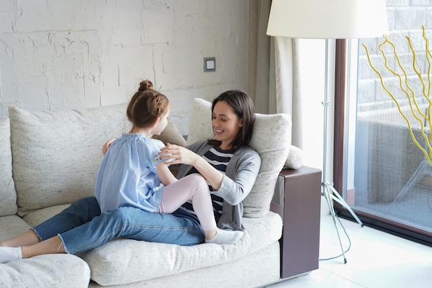 Słodkie małe dziecko córka śmiejąc się łaskotanie grając z matką na kanapie, szczęśliwa matka relaksująca zabawa z zabawnym małym dzieckiem dziewczynka wiązanie ciesząc się wypoczynkiem razem w salonie.