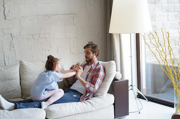 Słodkie małe dziecko córka śmiejąc się łaskotanie grając z tatą na kanapie, szczęśliwy ojciec relaksujący zabawę z zabawnym małym dzieckiem dziewczynka wiązanie ciesząc się wypoczynkiem razem w salonie.