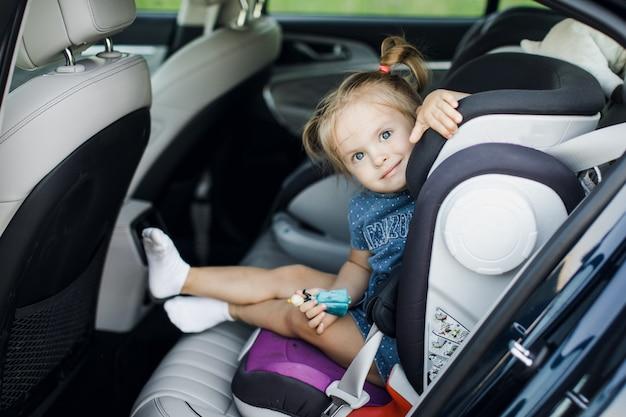 Słodkie małe dziecko dziecko siedzi w foteliku samochodowym