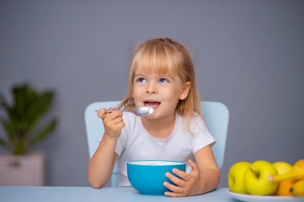 Słodkie małe dziecko dziewczynka jedzenie jogurtu w pomieszczeniu