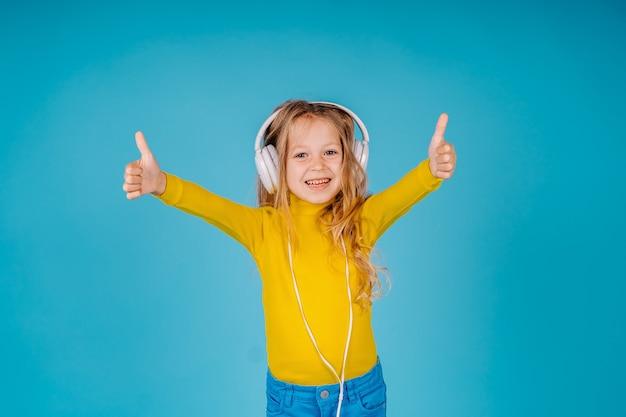 Słodkie małe dziecko dziewczynka słucha muzyki na dużych słuchawkach na białym tle i pokazuje dobry gest