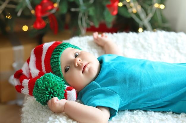 Słodkie małe dziecko leżące przed niewyraźnymi lampkami bożonarodzeniowymi