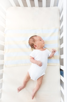 Słodkie małe dziecko leżące w białej kołysce w słoneczny dzień