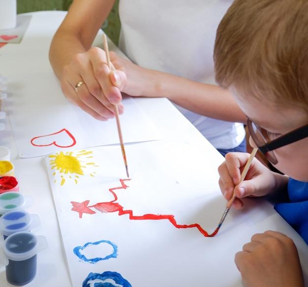 Słodkie małe dziecko maluje kreml przy stole z matką w zbliżeniu pokój gier