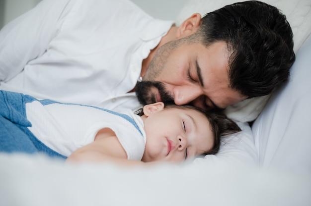 Słodkie małe dziecko odpoczywa i śpi wygodnie w domu na białym łóżku